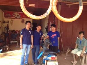Mr. S with Peuan Mit staff at his garage business in Kham Noi village.